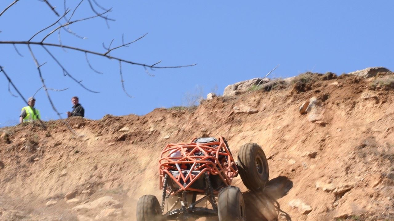 Orange off-road vehicle climbing dirt